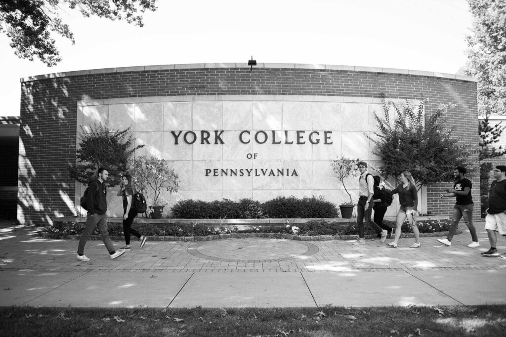 students walking past York welcome sign